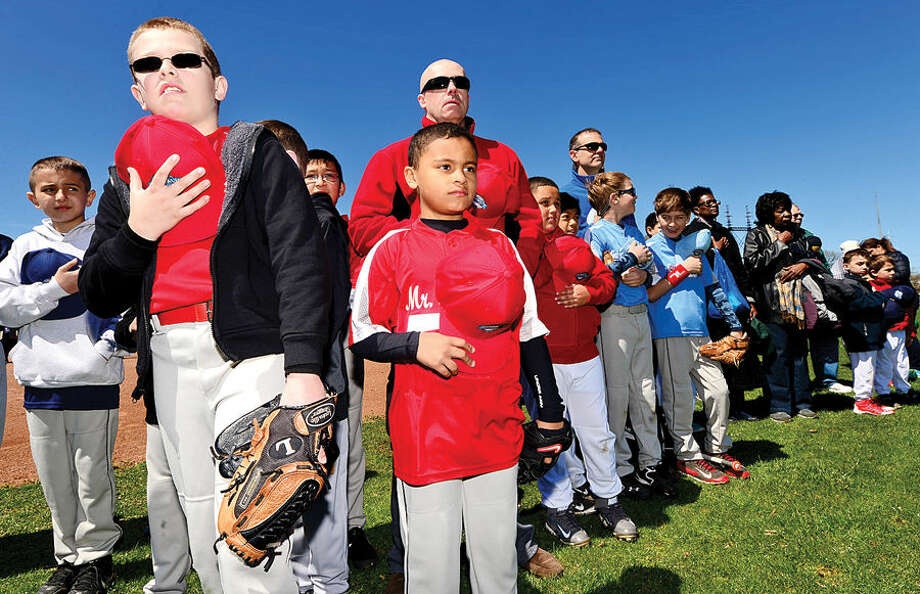Hour photo / Erik Trautmann Klaus Schroeder and Adrian Vega of the Mr. Frosty's team observe the National Anthem during the Norwalk Little League opening day ceremonies Saturday at Veteran's Park.