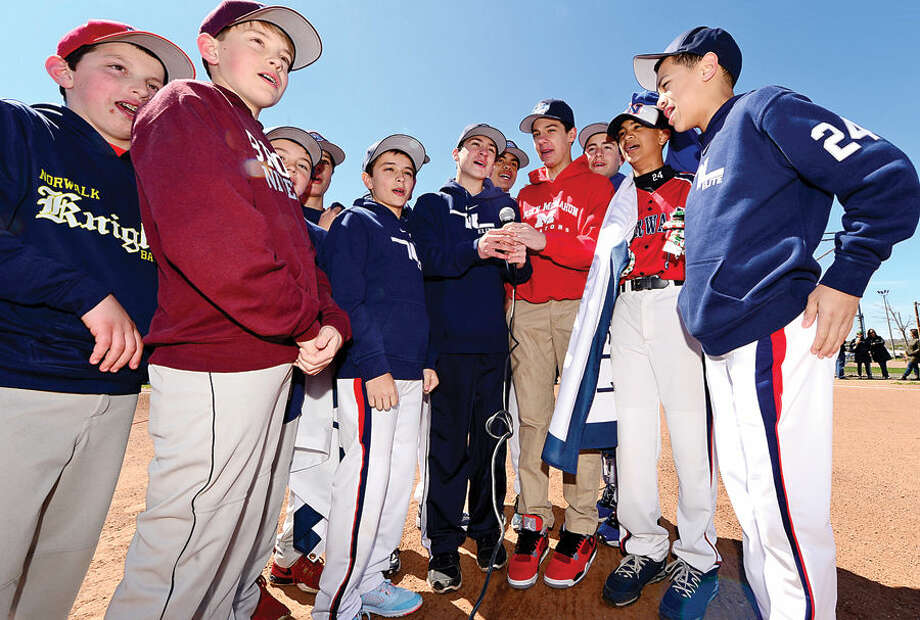 Hour photo / Erik Trautmann Members of the National champions 10 and under and the 12 and under teams recite the Little League pledge during the Norwalk Little League opening day ceremonies Saturday at Veteran's Park.