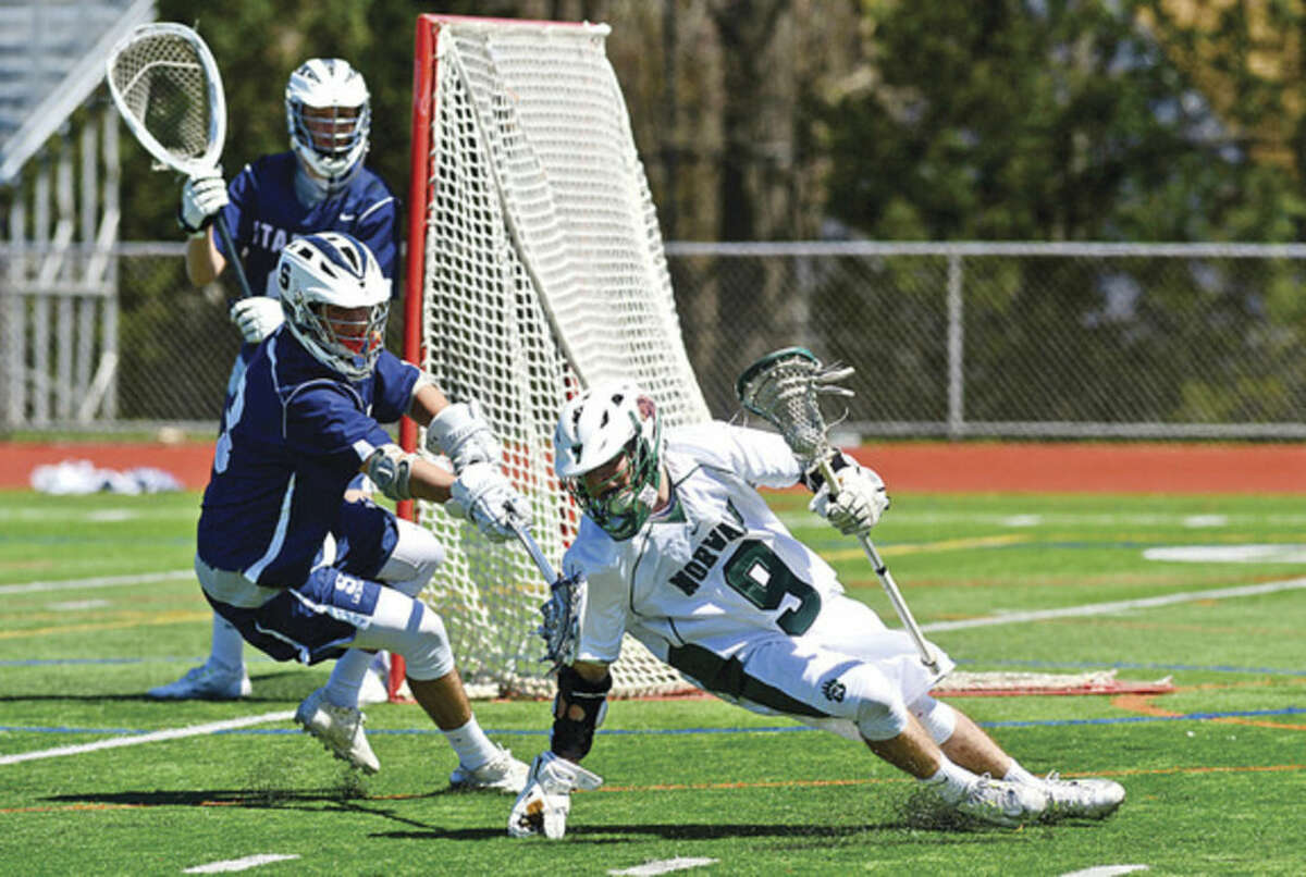 Hour photo/Erik Trautmann Norwalk's Zachary Grimm (9) regains his footing as the Bears take on Staples High School during their boys lacrosse match up at testa Field in Norwalk Saturday.