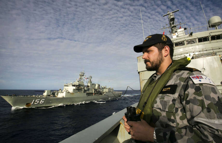 In this April 7, 2014 photo provided by the Australian Defence Force Able Seaman Steward Kirk Scott keeps watch on deck of HMAS Success as they conduct a replenishment at sea with HMAS Toowoomba, left, while both ships are deployed in the search of the missing Malaysia Airlines Flight 370 in the southern Indan Ocean. Authorities are confident that a series of underwater signals detected in a remote patch of the Indian Ocean are coming from the missing Malaysia Airlines plane's black boxes, Australia's prime minister said Friday, April 11. (AP Photo/Australian Defence Force, Julianne Cropley) EDITORIAL USE ONLY