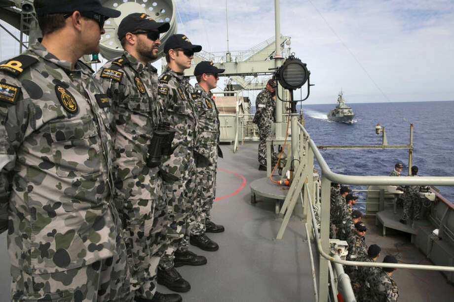 In this April 7, 2014 photo provided by the Australian Defence Force, HMAS Success crew members, from left, Sub Lt. Paul Connor, Able Seaman Michael Curtin, Marc Chandler and Midshipman Adrian Weatherby-Fell, line the upper decks as they conduct a replenishment at sea with HMAS Toowoomba, at back, while both ships are deployed in the search of the missing Malaysia Airlines Flight 370 in the southern Indian Ocean. Authorities are confident that a series of underwater signals detected in a remote patch of the Indian Ocean are coming from the missing Malaysia Airlines plane's black boxes, Australia's prime minister said Friday, April 11. (AP Photo/Australian Defense Force, Julianne Cropley) EDITORIAL USE ONLY