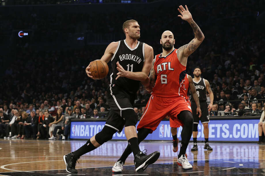 Brooklyn Nets center Brook Lopez (11) drives to the basket against Atlanta Hawks forward Pero Antic during the first half in Game 3 of a first-round NBA basketball playoff series, Saturday, April 25, 2015, at New York. (AP Photo/Mary Altaffer)