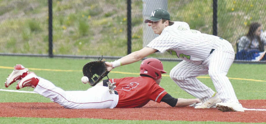 Norwalk first baseman Mike Gonzalez lunges for a pick-off attempt as a Fairfield Prep player dives safely back to first base during Saturday's game in Norwalk. Prep topped the host Bears, 4-0.