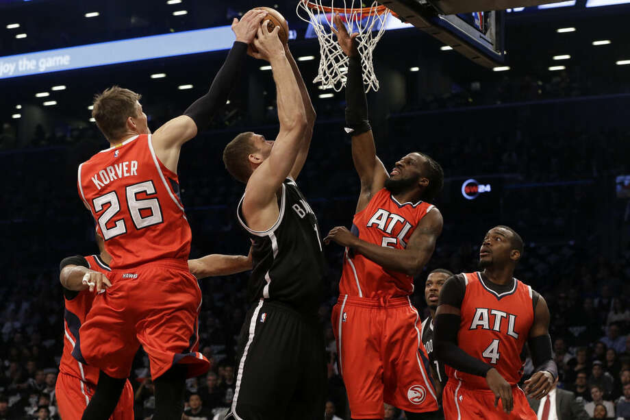 Atlanta Hawks guard Kyle Korver (26) and forward DeMarre Carroll (5) block Brooklyn Nets center Brook Lopez (11) during the first half in Game 3 of a first-round NBA basketball playoff series, Saturday, April 25, 2015, at New York. Hawks Paul Milsap (4) watches the action.(AP Photo/Mary Altaffer)