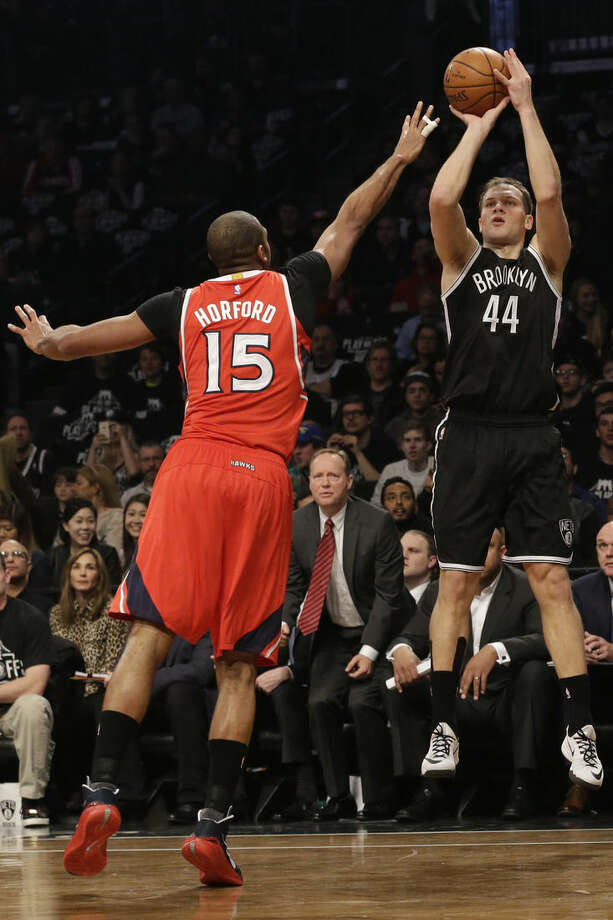 Brooklyn Nets guard Bojan Bogdanovic (44) shoots a 3-point goal past Atlanta Hawks center Al Horford (15) during the first half in Game 3 of a first-round NBA basketball playoff series, Saturday, April 25, 2015, at New York. (AP Photo/Mary Altaffer)