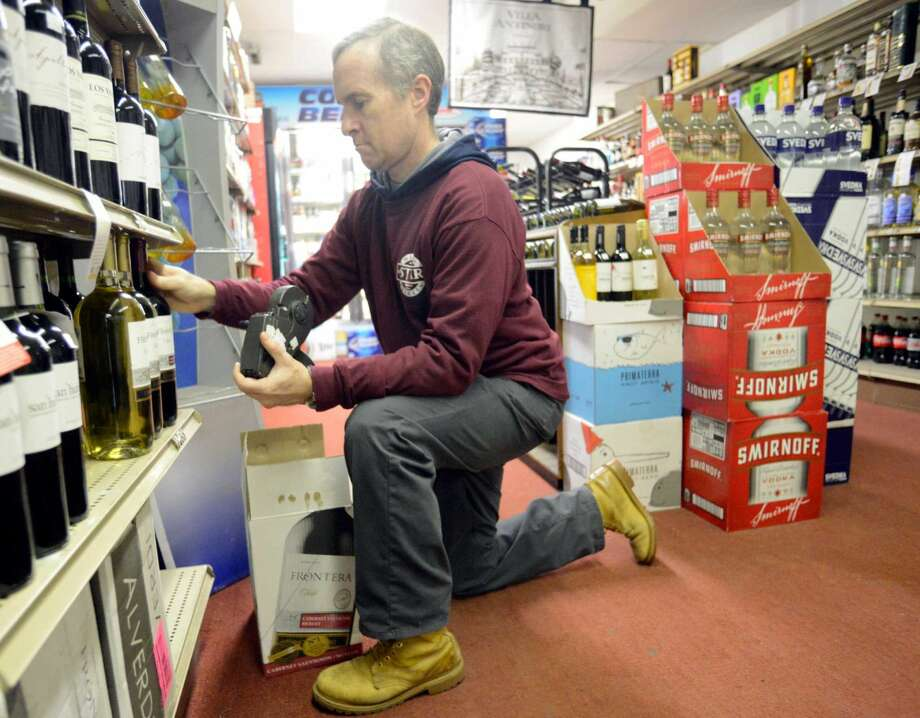 Bill Benison, manager of Star Wines & Spirits in Stamford on Tuesday, Feb. 23, 2016, restocks a shelf of wines. State officials are discussing eliminating minimum pricing for alcohol, which small business owners claim hurts them and favors big box retailers.