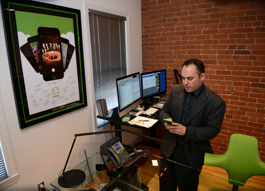 CEO Scott Howard works on his cell phone with his app called Peep, at the offices of Ingenuity Design in South Norwalk, Conn. on Wednesday August 2, 2014. Peep is a new app for photo taking and sharing.