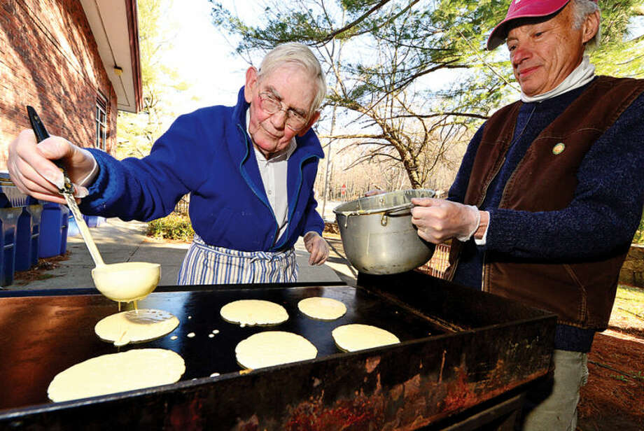 Hour photo / Erik Trautmann David Borglum and Robert Blachman make pancakes for The Silvermine Community Association Pancake Breakfast Saturday to benefit the Silvermine Scholarship fund. SCA has been awarding scholarships to community residents for 55 years. More than 300 high-school seniors have been helped on their way to higher education through this unique neighborhood program.
