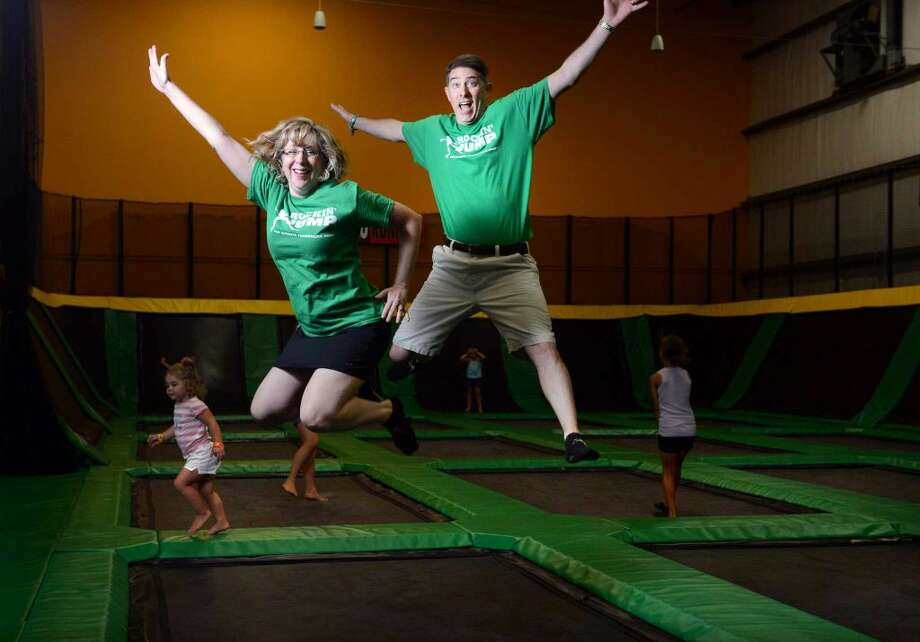 Owners Roni and Steve Rodier leap on the trampoline at ROCKINâÄô JUMP in Trumbull, Conn. Friday, Aug. 8, 2014.
