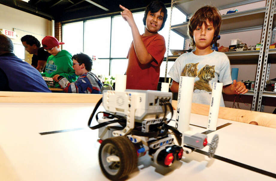 Hour photo / Erik Trautmann Aniruddh Rayachoti, 12, and Kai Weinstein, 10, learn to program a robot to navigate an obstacle course and complete various challenges using EV3 programming software during the Intro to Robotics with Lego Mindstorms at the Fairfield County Makers' Guild in Norwalk Saturday. Vladimir Mariano