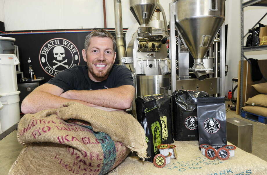 In this Monday, Sept. 21, 2015, photo, provided by QuickBooks, Michael Brown, owner of Death Wish Coffee Company, poses for a picture during Intuit QuickBooks Small Business Big Game finalists tour, in Round Lake, N.Y. Death Wish Coffee Co. won a competition held by software maker Intuit for a 30-second spot during the third quarter of the Super Bowl on Feb. 7, 2016. The Round Lake, N.Y., company beat more than 15,000 companies in voting by the public and Intuit employees. (Hans Pennink/QuickBooks via AP) ORG XMIT: NYBZ405