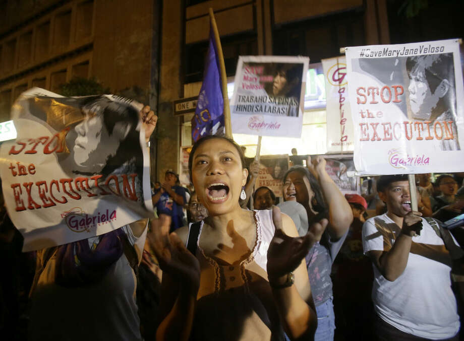 Protesters, who have been keeping vigil at the Indonesian Embassy in the financial district of Makati city east of Manila, Philippines, celebrate following an announcement of the delay of the execution of convicted Filipino drug trafficker Mary Jane Veloso in Indonesia, before dawn Wednesday, April 29, 2015. The execution was put off because her alleged boss had been arrested in the Philippines, and the authorities there requested Indonesian aid in pursuing the case. (AP Photo/Bullit Marquez)