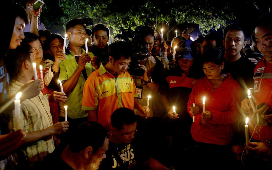 People hold candles to pray for death-row prisoners at Wijayapura port in Cilacap, Indonesia early Wednesday, April 29, 2015. Indonesia brushed aside last-minute appeals and executed eight people convicted of drug smuggling, according to foreign governments and local media reports Wednesday, although a Philippine woman was granted a stay of execution. (AP Photo/Tatan Syuflana)