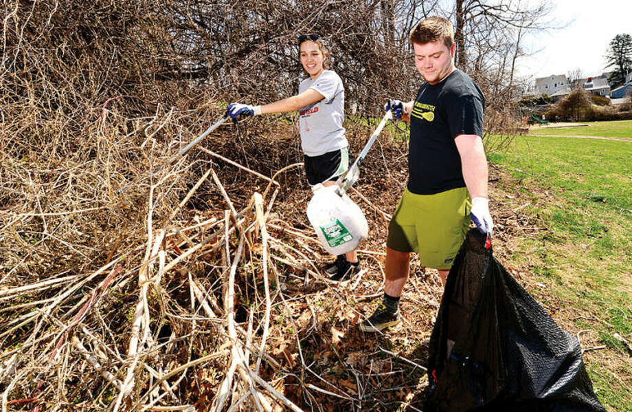 Hour photo / Erik Trautmann Students from Fairfield University Gabby Lopez and Ben Bayers help clean up Flax Hill Park as part of the Keep Norwalk Beautiful intiative Saturday.