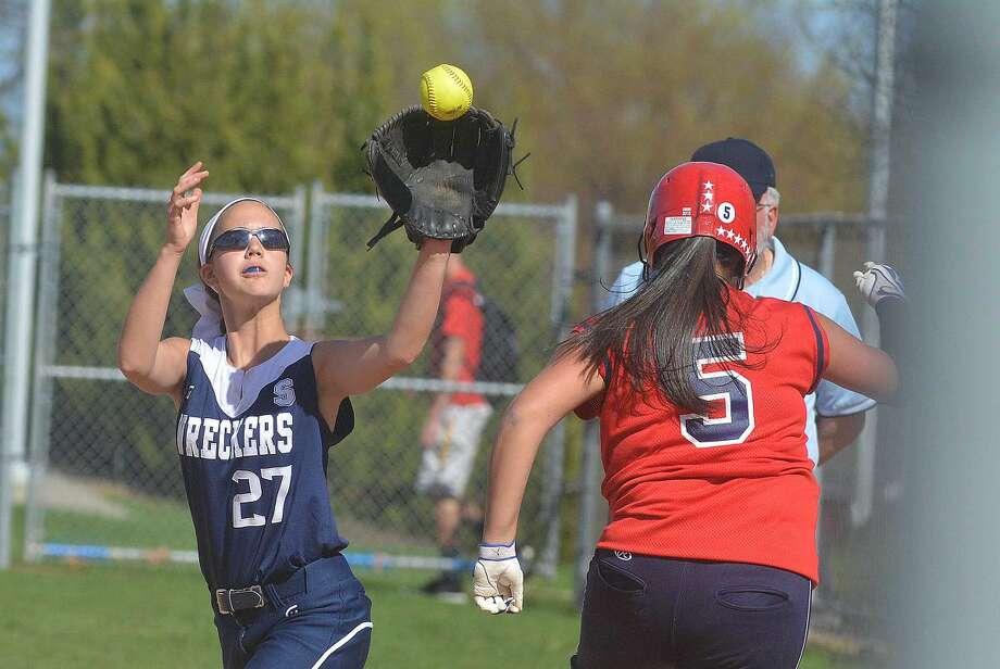 Staples' Taylor Rochlin catches a throw as McMahon's Tori Rodriguez runs through the base. (Hour Photo/Alex von Kleydorff)