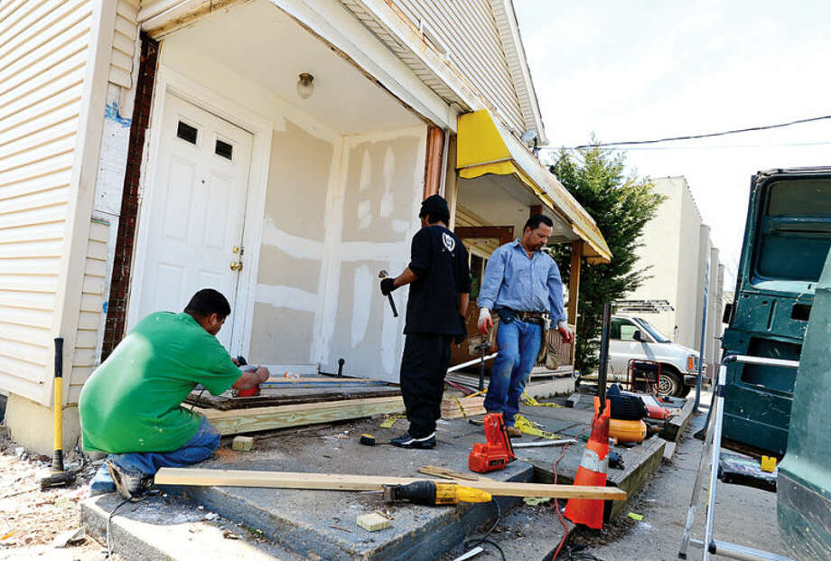 Hour photo / Erik Trautmann Workers with B&B Constuction repair the porch of 39 Butler St after a car slammed into the building early Saturday morning.