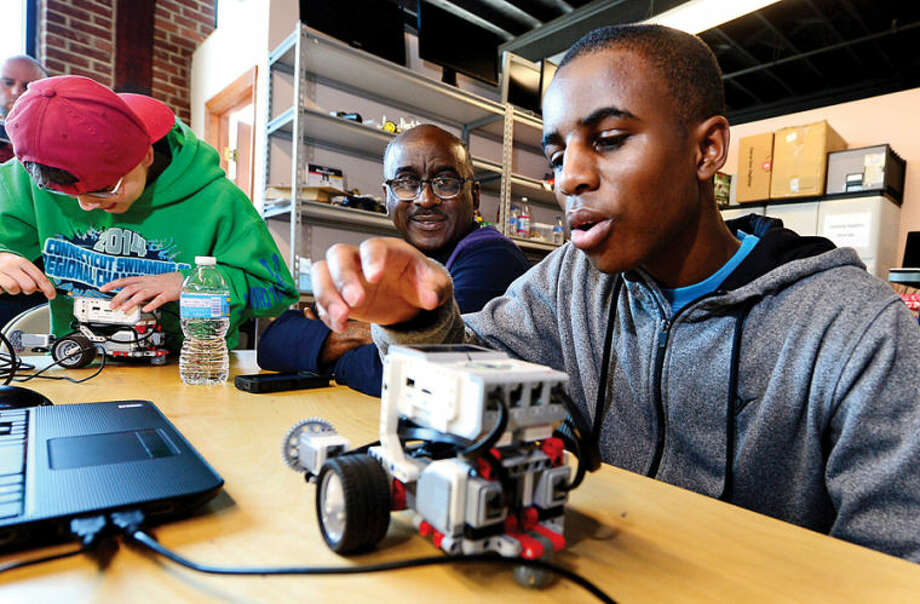 Hour photo / Erik Trautmann Josh Mitchell, 15, and his dad, Maurice Mitchell, learn to program a robot to navigate an obstacle course and complete various challenges using EV3 programming software during the Intro to Robotics with Lego Mindstorms at the Fairfield County Makers' Guild in Norwalk Saturday. Vladimir Mariano