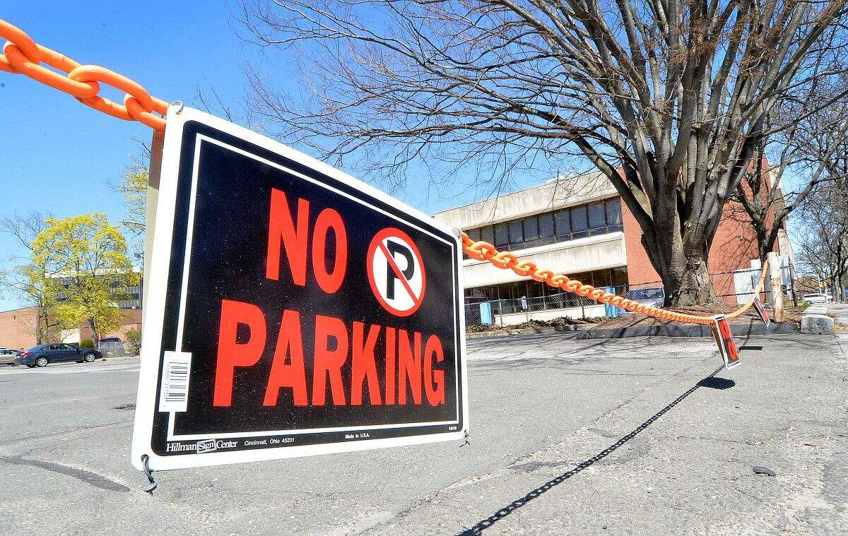 Hour Photo/Alex von Kleydorff Signs hang on a chain closing a parking lot next to the library on Mott Ave in Norwalk