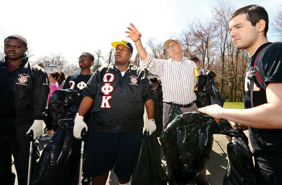 Hour photo / Erik Trautmann Keep Norwalk Beautiful Executive Director and Golden Hill Association president Jim Del Greco directs studenys from Faifield University as they help clean up Flax Hill Park as part of the Keep Norwalk Beatiful intiative Saturday.