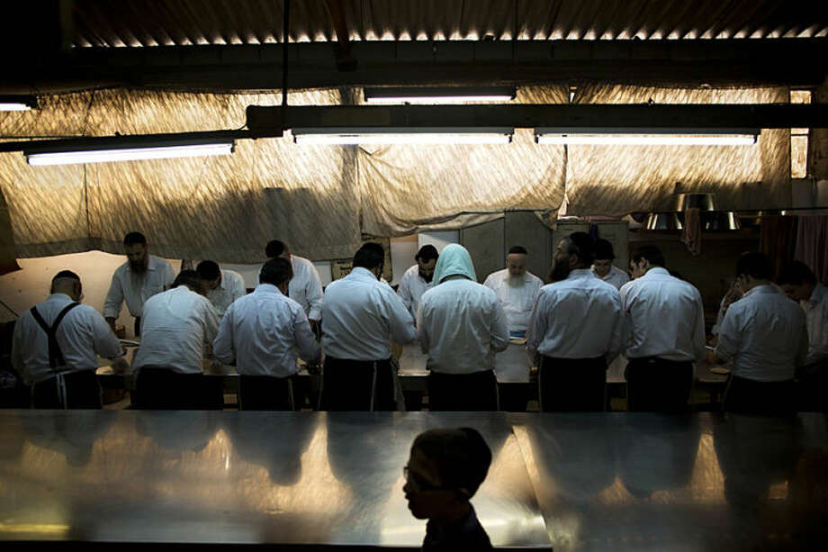 Ultra-Orthodox Jews prepare special matzoh, a traditional handmade Passover unleavened bread, at a bakery in Bnei Brak near Tel Aviv, Israel. Thursday, April 10, 2014. Jews are forbidden to eat leavened foodstuffs during the Passover holiday. Passover celebrates the biblical story of the Israelites' escape from slavery and exodus from Egypt. (AP Photo/Oded Balilty)