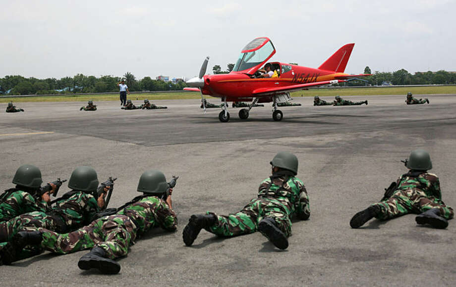 Indonesian soldiers train their weapons at an airplane piloted by 65 year-old Heinz Peier of Switzerland after it was intercepted by Indonesian jet fighters and forced to land at Soewondo Air Base in Medan, North Sumatra, Indonesia, Thursday, April 10, 2014. Peier was on a ferry flight from Colombo to Singapore when he entered Indonesian airspace illegally, an Air Force official said. (AP Photo/Binsar Bakkara)