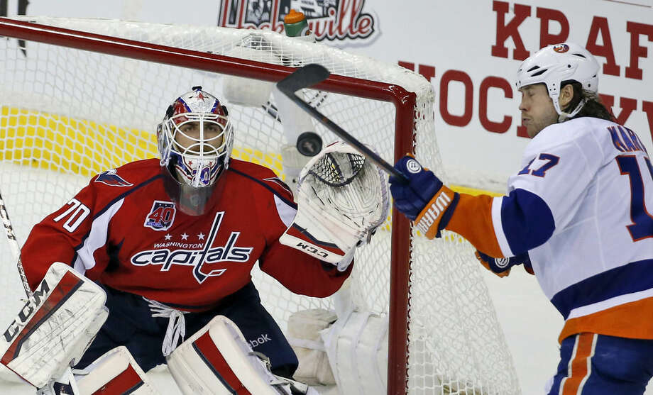 Washington Capitals goalie Braden Holtby (70) keeps his eye on the puck as New York Islanders left wing Matt Martin (17) attempts to deflect it during the third period of Game 7 in the first round of the NHL hockey Stanley Cup playoffs, Monday, April 27, 2015, in Washington. The Capitals won 2-1, to advance. (AP Photo/Alex Brandon)