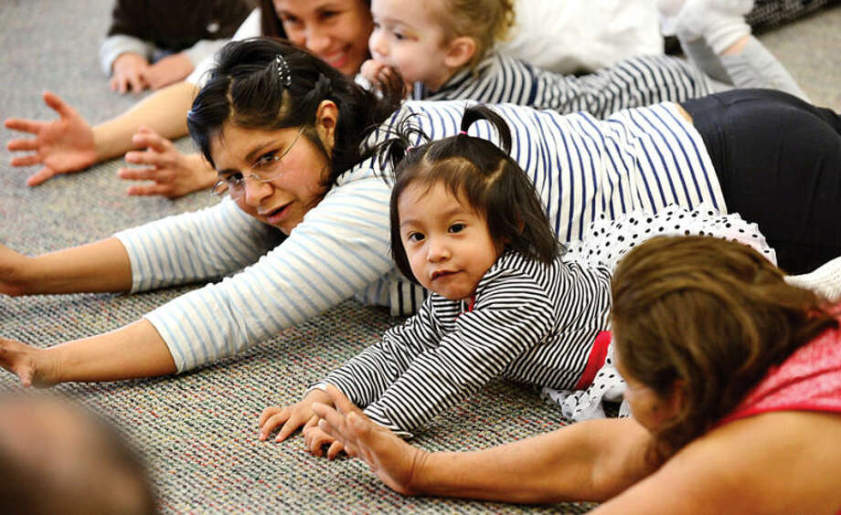 Hour photo / Erik Trautmann Yolanda Chalini and her daughter Stephany Chalini, 2, participate in Yoga for Kids and Caregivers with Mark at the Norwalk Pubic Library Friday as part of a program featured the second Friday of every month.