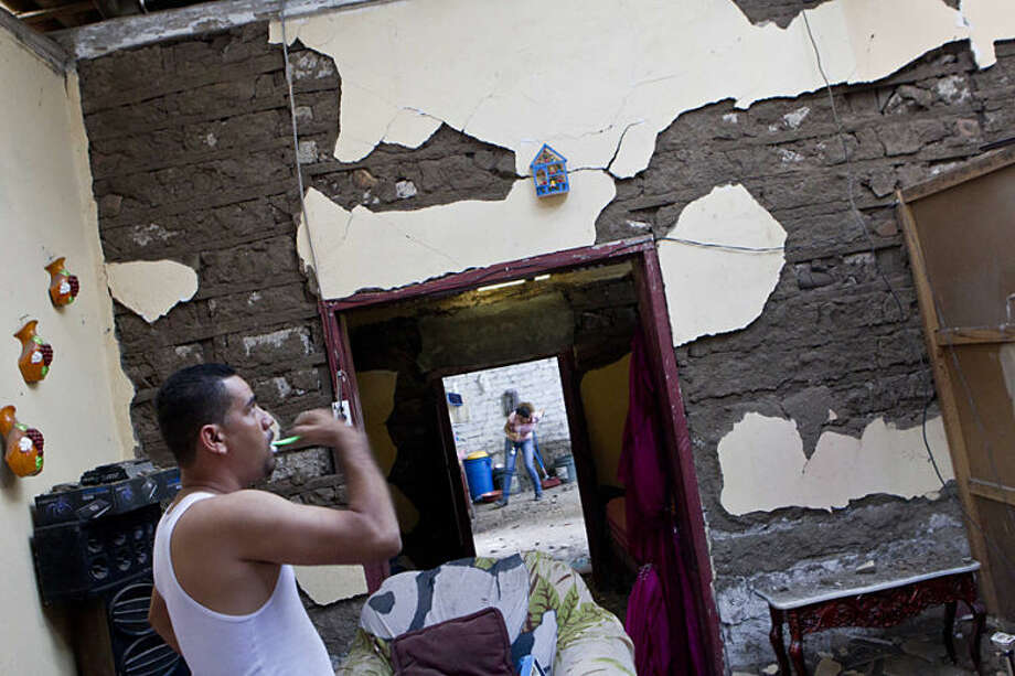 A man brushes his teeth inside his home, damaged by an earthquake in Nagarote, Nicaragua, Friday, April 11, 2014. Nicaragua's President Daniel Ortega declared red alert Friday after an earthquake of 6.2 magnitude on the Richter scale that shook the country on Thursday and left one dead, hundreds of houses damaged and thousands of people affected . (AP Photo/Esteban Felix)