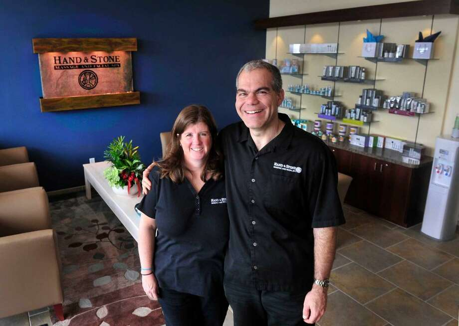 Marianne and Rob Durr stand inside Hand & Stone Massage and Facial Spa, the Brookfield, Conn., business they own, Friday, Aug. 30, 2013.