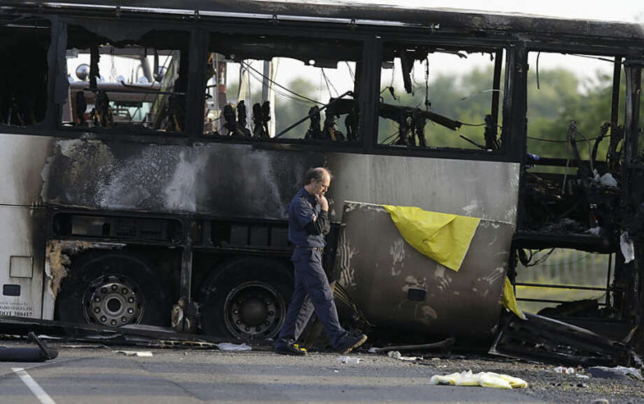 An official walks past the remains of a tour bus that was struck by a FedEx truck on Interstate 5 Thursday in Orland, Calif., Friday, April 11, 2014. At least ten people were killed and dozens injured in the fiery crash between the truck and a bus carrying high school students on a visit to a Northern California College. (AP Photo/Jeff Chiu)