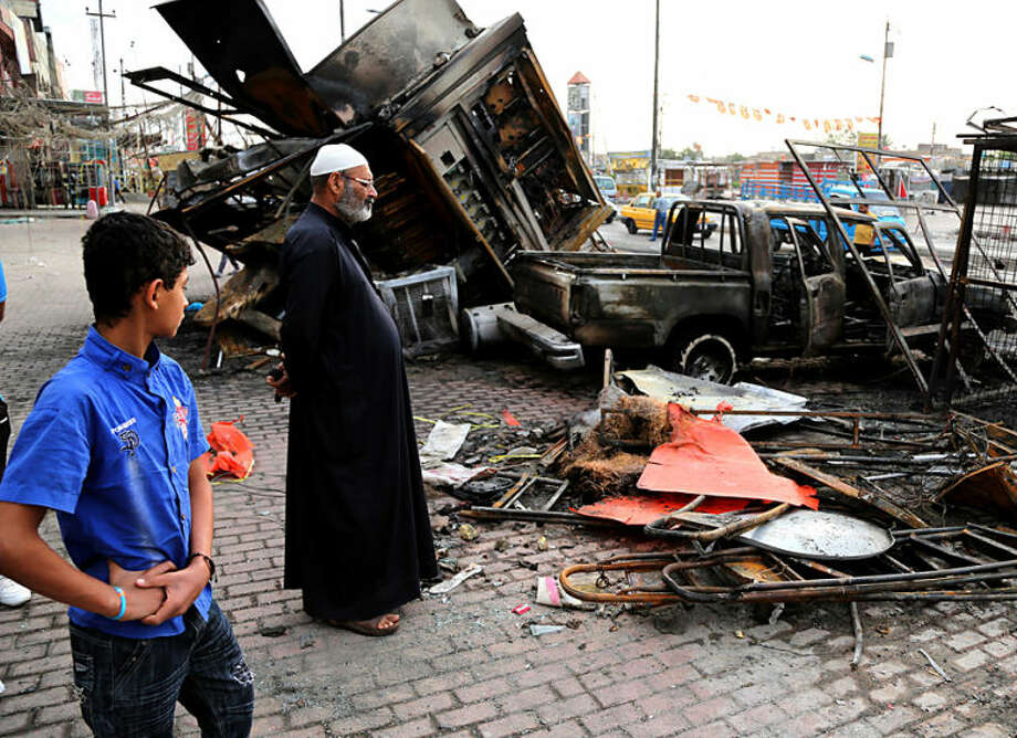 Iraqi civilians inspect debris left in the aftermath of a car bombing on a commercial street in Baghdad's eastern neighborhood of Sadr City, Iraq, Friday, April 11, 2014. Two car bombs exploded in Shiite neighborhoods of Iraq's capital Thursday night, killing and wounding scores of people, as violence roars on before a crucial election later this month, authorities said. Last year, Iraq weathered its deadliest bout of violence since it pulled back from the brink of civil war in 2008. (AP Photo/Karim Kadim)