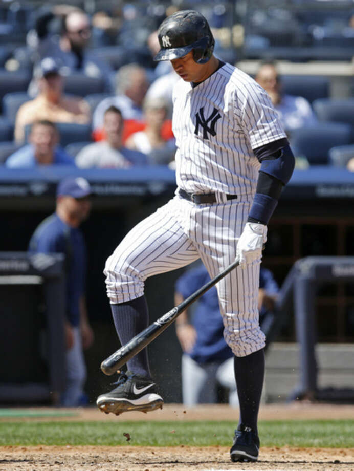 New York Yankees designated hitter Alex Rodriguez taps his bat on his shoe after striking out in the fourth inning of a baseball game at Yankee Stadium in New York, Wednesday, April 29, 2015. (AP Photo/Kathy Willens)