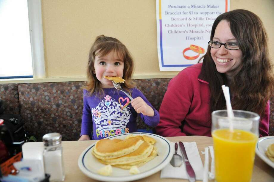 Mackenzie Shibley, 2, and her mom, Rebecca Shibley enjoy pancakes at the IHOP on Wolf Road during National Pancake Day on Tuesday, March 3, 2015, in Colonie, N.Y. For every short stack of buttermilk pancakes served on National Pancake Day IHOP guests are invited to make a voluntary donation to the Bernard & Millie Duker Children's Hospital at Albany Med. For the 10th consecutive year, Capital District IHOP restaurants will offer guests a free short stack of buttermilk pancakes on Tuesday, March 3, National Pancake Day. (Paul Buckowski / Times Union)