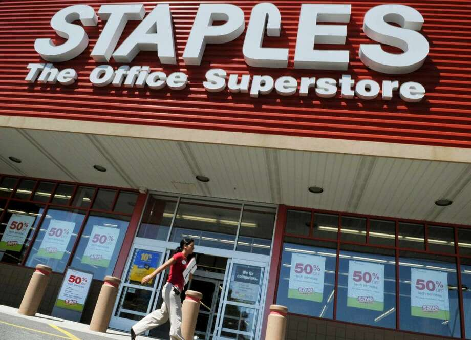 FILE - In this May 26, 2009 file photo, a woman walks past a Staples office supply store in Danvers, Mass. Staples on Wednesday, Feb. 4, 2015 announced it is buying Office Depot in a cash-and-stock deal valued at nearly $6 billion.