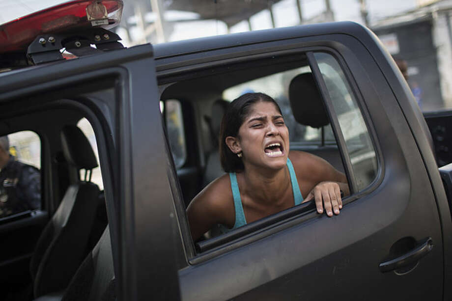 A woman screams after being detained during protests near the area recently occupied by squatters in Rio de Janeiro, Brazil, Friday, April 11, 2014. The woman was later released. Squatters in Rio de Janeiro are clashing with police after a Brazilian court ordered that 5,000 people be evicted from abandoned buildings of a telecommunications company. Officers have used tear gas and stun grenades to try to disperse the families. (AP Photo/Felipe Dana)