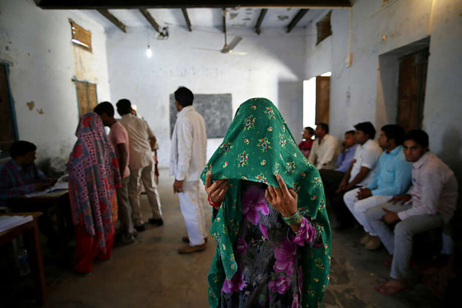A woman holds a veil over her face and waits for her identity card to be checked before she is allowed to vote in Chandeni, in the northern Indian state of Haryana, Thursday, April 10, 2014. Indians voted in the crucial third phase of national elections Thursday, with millions going to the polls in the heartland states that are essential to the main opposition Hindu nationalist party's bid to end the 10-year rule of Congress party. (AP Photo/Saurabh Das)