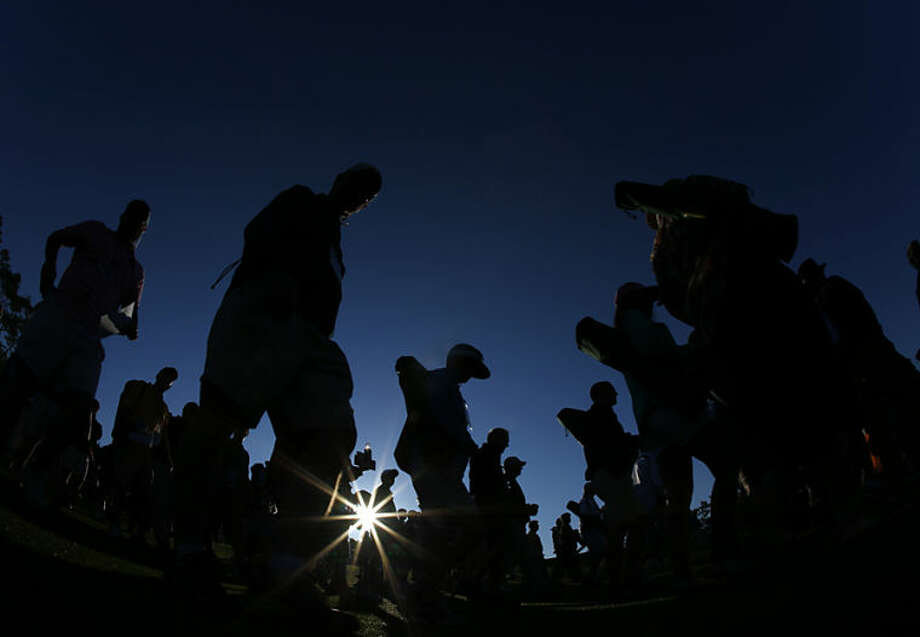 Spectators make their way down the first fairway at sunrise for the first round of the Masters golf tournament Thursday, April 10, 2014, in Augusta, Ga. (AP Photo/Matt Slocum)
