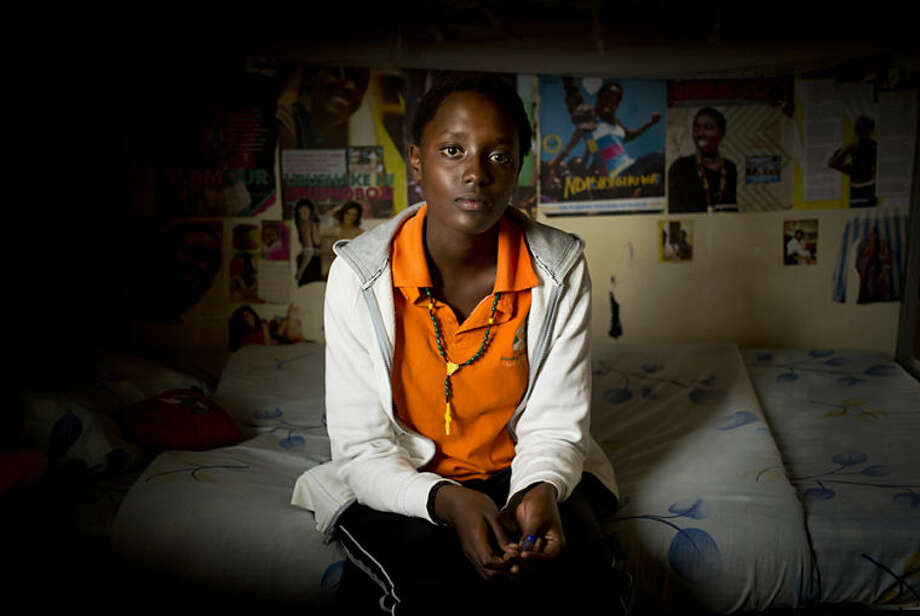 In this photo taken Monday, March 24, 2014, student Sharon Kalisa, 17, whose favorite subject is history and particularly genocide studies, sits in her bedroom at the Agahozo-Shalom Youth Village near Rwamagana, in Rwanda. Most of the kids in a Rwandan school set amid the lush green, rolling hills of eastern Rwanda don't identify themselves as Hutu or Tutsi. That's a positive sign for Rwanda, which is now observing the 20th anniversary of its genocide, a three-month killing spree that, according to the official Rwandan count, left more than 1 million people dead, most of them Tutsis killed by Hutus. The teenagers attending the Agahozo-Shalom Youth Village, a school with dorms that creates tight-knit student families, say the ethnic slaughter that their parents or grandparents were a part of either as victims or perpetrators won't be repeated. The school director echoes the sentiment. (AP Photo/Ben Curtis)