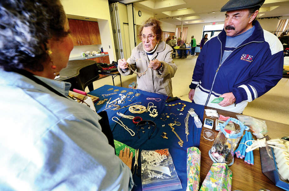 Hour photo / Erik Trautmann Rose Hliva and her son Donald Casavecchio haggle over jewelery during the Norwalk United Methodist Church annual Tag Sale Friday. The sale continues saturday 10 am to 1pm.
