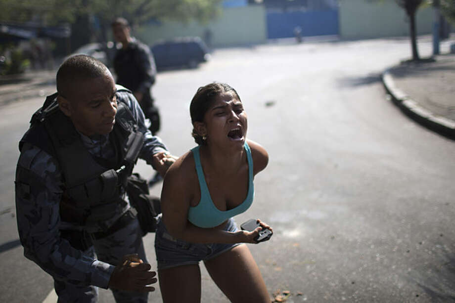 A woman screams while being detained during protests near the area recently occupied by squatters in Rio de Janeiro, Brazil, Friday, April 11, 2014. The woman was later released. Squatters in Rio de Janeiro are clashing with police after a Brazilian court ordered that 5,000 people be evicted from abandoned buildings of a telecommunications company. Officers have used tear gas and stun grenades to try to disperse the families. (AP Photo/Felipe Dana)