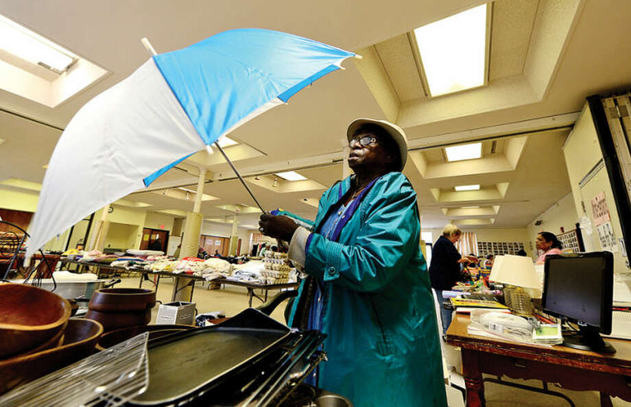 Hour photo / Erik Trautmann Gloria Lawrence makes sure an umbrella is in working order during the Norwalk United Methodist Church annual Tag Sale Friday. The sale continues saturday 10 am to 1pm.