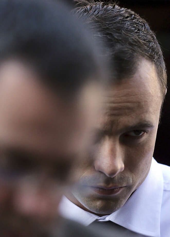 Oscar Pistorius arrives at the high court in Pretoria, South Africa, Friday, April 11, 2014. The chief prosecutor laughed scornfully at an answer from Pistorius during the Olympic athlete's murder trial Thursday, mocking the man who shot his girlfriend. Pistorius is charged with murder for the shooting death of his girlfriend, Reeva Steenkamp, on Valentine's Day in 2013. (AP Photo/Themba Hadebe)