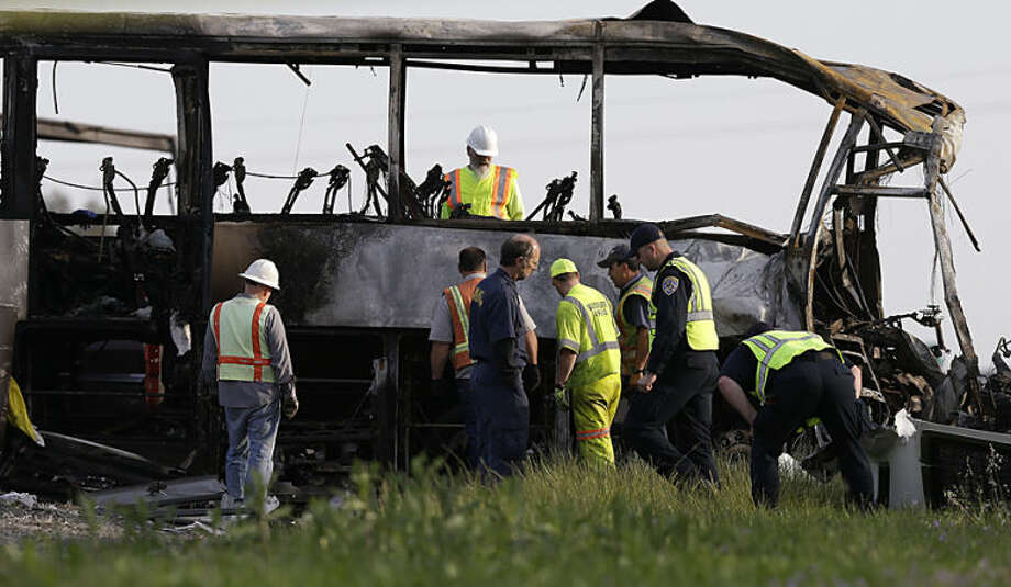 Officials and California Highway Patrol Officers look over the remains of a tour bus that was struck by a FedEx truck on Interstate 5 Thursday in Orland, Calif., Friday, April 11, 2014. At least ten people were killed and dozens injured in the fiery crash between the truck and a bus carrying high school students on a visit to a Northern California College. (AP Photo/Jeff Chiu)