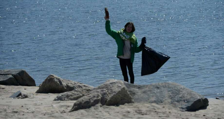 Caroline Steib, a sixth-grader at King Academy, collects garbage along the main beach at Cove Island Park in Stamford on Saturday. Steib, along with a group of families from the school in Stamford, participated in King Cares Day, where students volunteer to complete two hours of community service. The group of 20 collected over 300 pounds of trash, that included plastics, discarded diapers, fishing lines and broken pieces of Styrofoam.