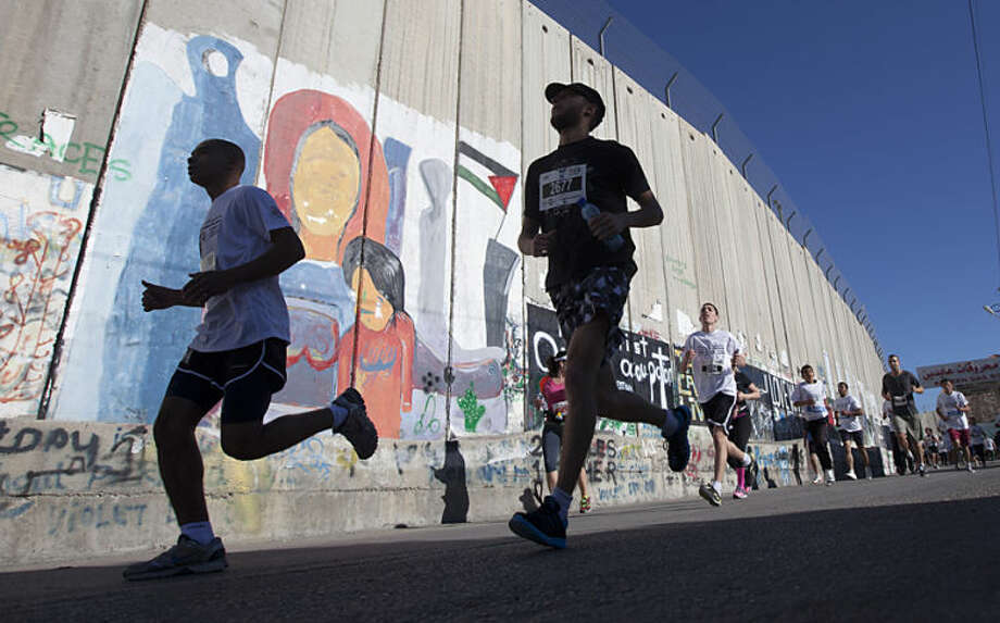 """Palestinians and foreigners, including activists, run past the separation barrier during the second annual Palestine International Marathon in the West Bank town of Bethlehem, Friday, April 11, 2014. About 1,000 people participated in the race. Israel barred 30 runners, including an Olympic athlete, from leaving the Gaza Strip to participate in the marathon, highlighting Israel's tight restrictions on travel in and out of the Hamas-ruled territory, Palestinian officials said Tuesday. Maj. Guy Inbar, an Israeli defense official, said the Bethlehem marathon sponsored by the Palestinian Authority """"has political overtones,"""" but did not elaborate. (AP Photo/Majdi Mohammed"""