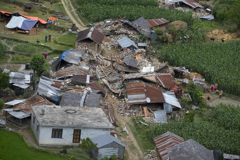 Houses on the higher reaches of mountains destroyed in Saturday's earthquake are seen from a helicopter near Dhadingbesti, in Nepal, Wednesday, April 29, 2015. The first aid shipments reached a hilly district near the epicenter of Nepal's earthquake, a U.N. food agency official said, and distribution of food and medicine would start Wednesday, five days after the quake struck. (AP Photo/Manish Swarup)