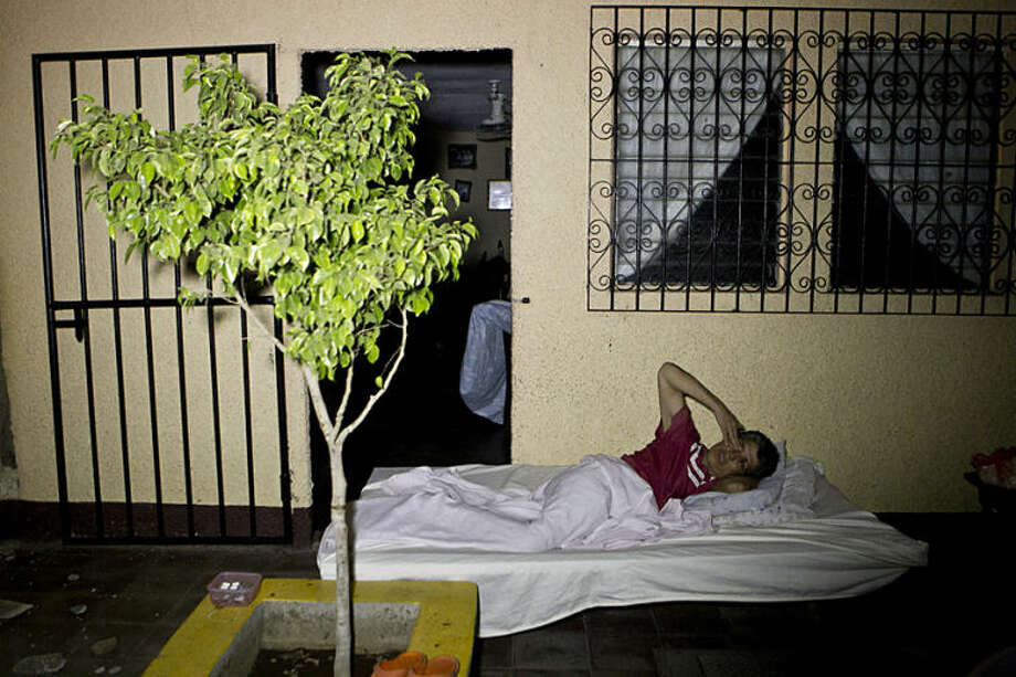 A woman lies on a mattress outside her home after a strong earthquake hit Nagarote, Nicaragua, late Thursday, April 10, 2014. A 6.1-magnitude earthquake damaged dozens of houses in western Nicaragua on Thursday, and authorities said some people were injured by falling ceilings, beams and walls. (AP Photo/Esteban Felix)