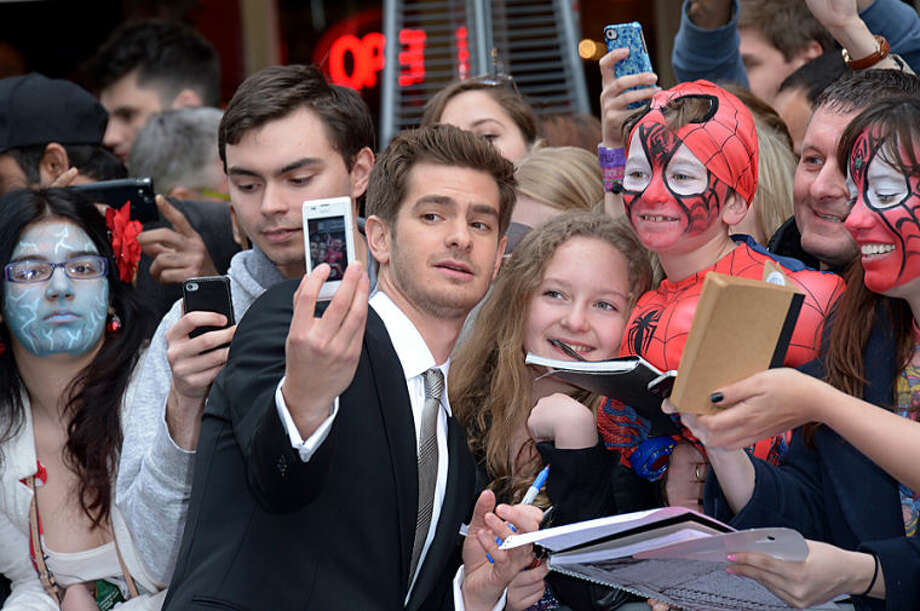 British actor Andrew Garfield takes a 'selfie' with fans as he arrives on the red carpet for the world premiere of The Amazing Spider-Man 2 in Leicester Square, London, Thursday April 10, 2014. (Photo by Jon Furniss/Invision/AP)