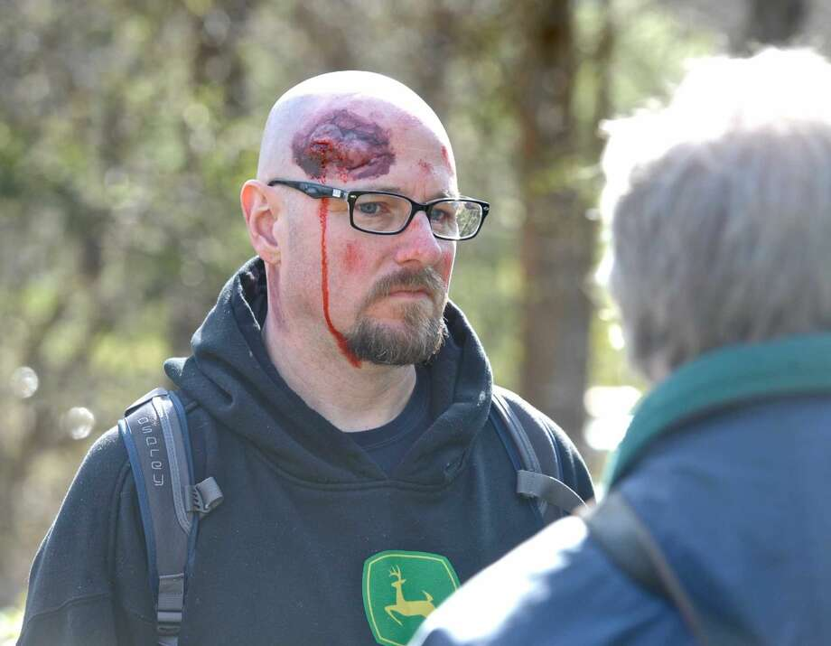 Todd Forkin, of Woodbury, gets instructions before heading out into Clatter Valley Park to play the part of a victim in a search and rescue drill in the park on Saturday, April 16, 2016, in New Milford, Conn. Forkin, who works in the Danbury Hospital ER Department had makeup applied to simulate a head injury.