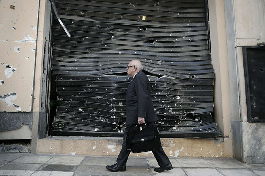 A man walks past a damaged shutter a day after a car bomb went off, in Athens, on Friday, April 11, 2014. A bomb exploded outside a Bank of Greece building in central Athens before dawn Thursday, causing some damage but no injuries. The attack came as financially stricken Greece returns to borrowing on the international bond market for the first time in four years. (AP Photo/Petros Giannakouris)